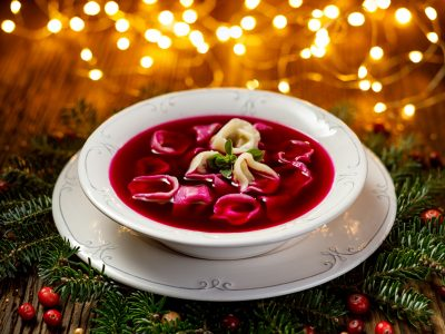 Christmas beetroot soup, red borscht with small dumplings with mushroom filling in a ceramic white plate on a wooden table .Traditional Christmas eve dish in Poland.