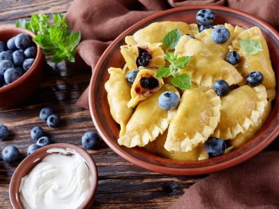 sweet dumplings, pierogi, vareniki with blueberry fillings in a clay bowl on a dark rustic table with sour cream and fresh berries, horizontal view from above, close-up
