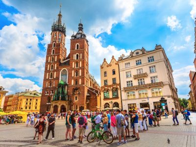 Krakow, Poland - June 18, 2019: Panoramic day view of main market square Rynek Glowny with St Mary Basilica with tourists