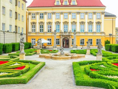 Wroclaw/Poland- August 18, 2017: View of the Royal Palace – History museum - baroque style building and beautiful garden with sculptures in a courtyard.